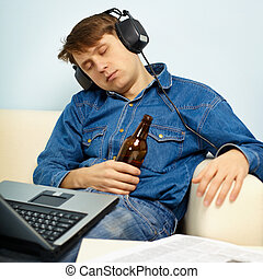 Man fell asleep at home on couch with a beer - A young man...
