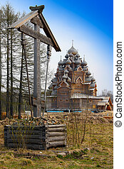 Cross before Wooden orthodox church in name of Cover All-holy mother of God, Russia (Pokrovskaya church)