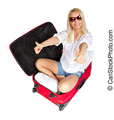 Woman showing thumbs up in travel suitcase packed for...
