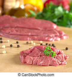 Fresh raw beef meat with parsley on top, with vegetables,...