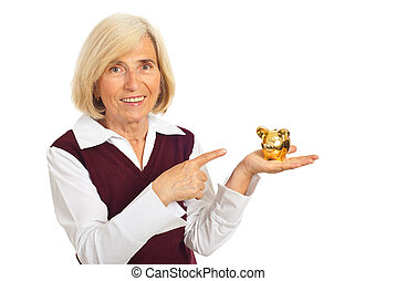 Happy senior woman pointing to piggy bank isolated on white...