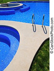 blue tiles swimming pool with green grass garden around