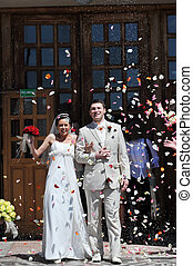 Newly wed couple being showered in rose petals