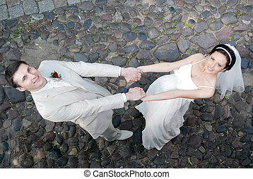 groom and  bride in  white dress dance on sidewalk