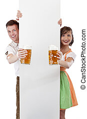 Young Bavarian man and girl in dirndl with adspace and beer stein