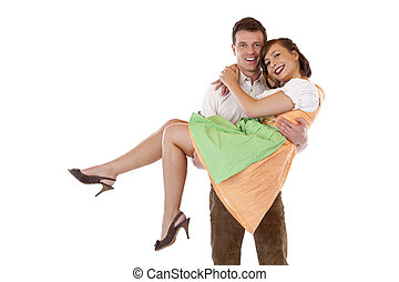 Bavarian man carries woman with dirndl on his arms and smiles