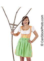 Young beautiful woman with dirndl holds pitchfork and smiles.