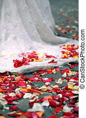 rose petals on ground near wedding dress