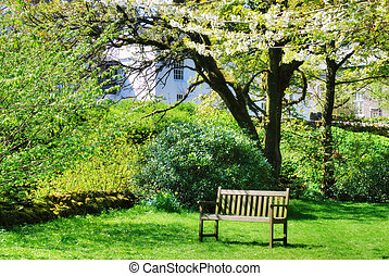 Bench in an English contry garden - A wooden bench in an...
