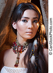 Portrait of American Indian female looking from tent -...