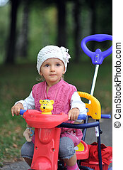 small girl with tricycle close up