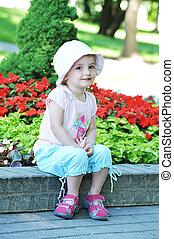 little girl sitting on  park bench
