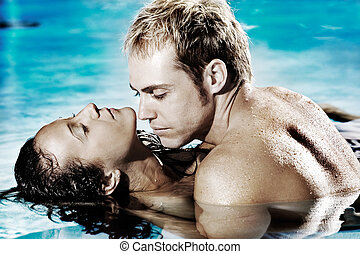 Sexy couple in pool - Young sexy couple in pool holding each...