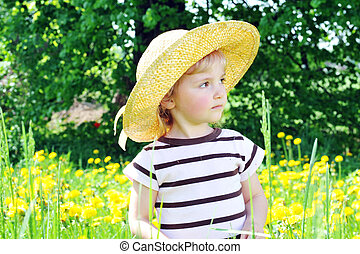 girl in blossoming field - little girl in straw hat walks on...