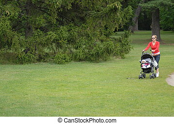 Young mother with child goes on grass