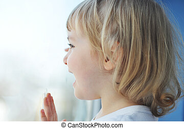 girl sits at window - cheerful little girl sits at window...