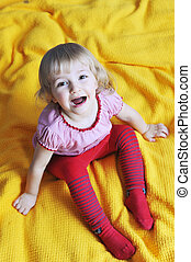 girl sits on bed - cheerful little girl sits on bed of...