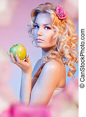 Curly blond woman with green apple holding a green apple and...