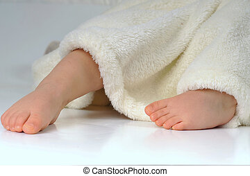 feets of little girl in white towel