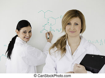 Two scientists looking at the camera while being in front of a white board in a lab