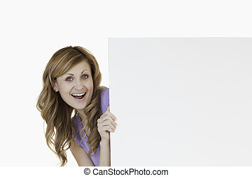 Smiling blond-haired woman holding a white board