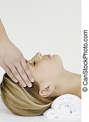 Blond-haired woman receiving a spa treatment while lying...