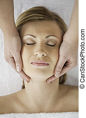 Beautiful blond-haired woman getting a massage on her face
