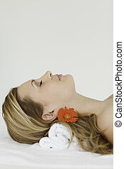 Young and attractive blond-haired woman lying down while...