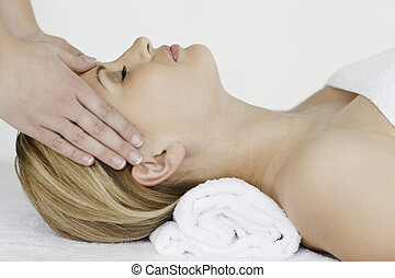 Young blond-haired woman receiving a spa treatment