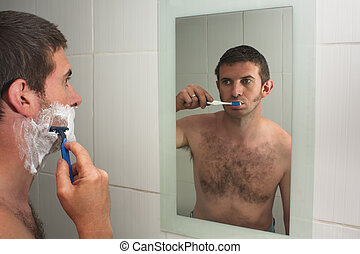 Multitasking - A male shaving in a bathroom mirror whilst...