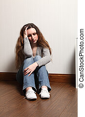 Depressed and alone a teenage girl sits on floor - Teenage...