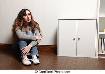Anxious teenage girl sits alone on floor at home - Looking...