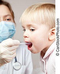 Child taking a medicine - Doctor giving a spoon of syrup to...