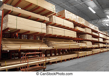 Wood in lumber yard - Wood stacked on shelving inside a...