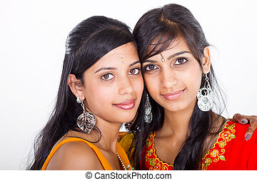 two young indian women in traditional sari in studio