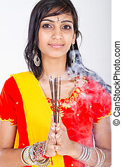 young indian woman holding incense, studio portrait
