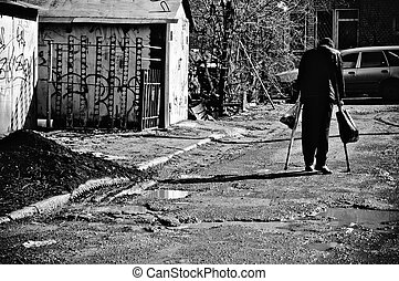 A sick poor man with crutches walking down the street. Rear...