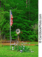 An American flag,windmill and birdbath among a group of new...