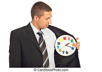 Business man checking the time and holding a clock in...