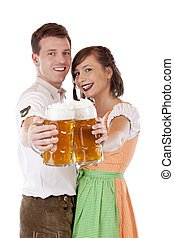 Young Bavarian couple in love hold Oktoberfest stein saying...