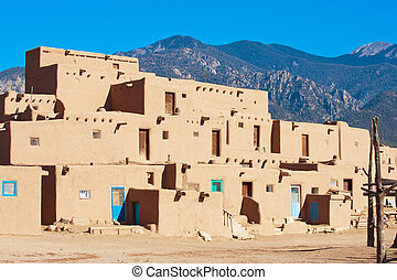 Taos Pueblo - Ancient Taos Pueblo with mountains on...