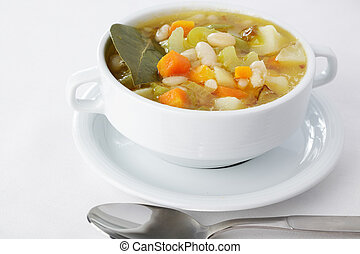 Minestrone in white bowl with bay leaf