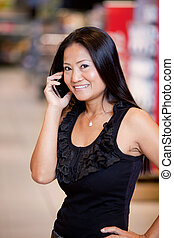 Woman Using Mobile Phone - An asian woman talking on a...