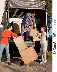 Moving Team - A group of people moving boxes from a trailer