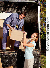 Moving Truck Couple - A happy couple moving boxes from a...