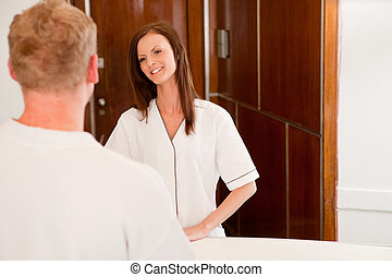 Spa Recption - A spa receptionist helping a man at the...