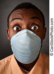 Wide-eyed man in surgical mask - Wide-eyed Black man wearing...