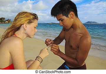 man places a bandage on a finger - Hawaiian man places a...