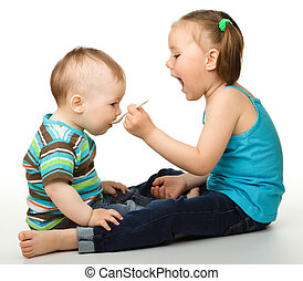 Sister is feeding her little brother using spoon, isolated...