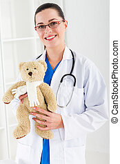 pediatrician with teddy bear - young female pediatrician...